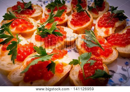 Food. Sandwiches with red caviar. White bread smeared on which salmon roe on top is leaf green.