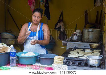 SUCHITOTO EL SALVADOR - MAY 07 : Salvadoran woman prepares Popusas in Suchitoto El Salvador on May 07 2016. Popusa is a traditional Salvadoran dish made of corn tortilla