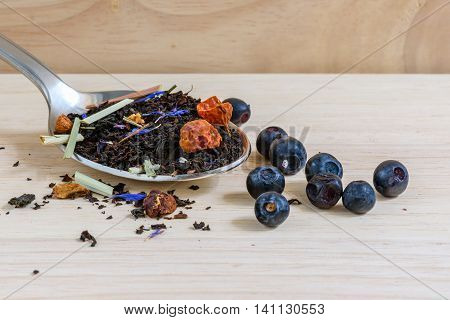 Dry black tea on spoon with blueberries. It is tasty healthy and very flavored. Good choice for morning
