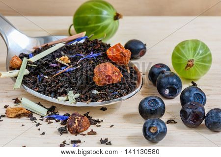 Black tea with different fruits and berries for breakfast. It is tasty healthy and very flavored. Good beginning of the day