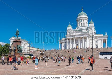 HELSINKI FINLAND - JULY 19 2016: Many tourists near statue of Alexander II on the Senate Square
