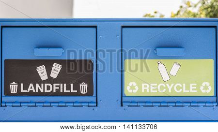 A blue trash container with two openings, landfill or recycle