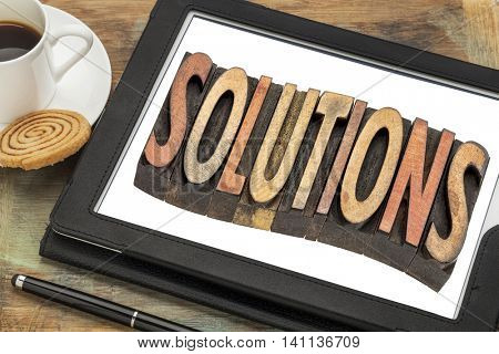 solutions word  - text in vintage letterpress  wood type printing blocks on a digital tablet with cup of coffee
