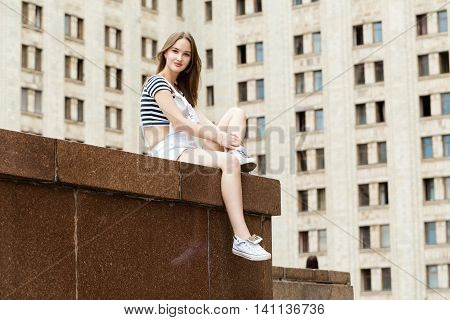 Young, beautiful woman sitting on stairs near the university