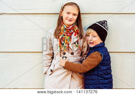 Outdoor portrait of two cute kids on a nice sunny autumn day