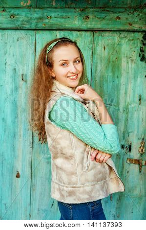 Outdoor portrait of a young woman wearing beige waistcoat and turquoise pullover, standing next to old door, vertical image