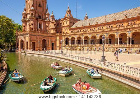 Seville, Andalusia, Spain - April 18, 2016: panoramic view of boats with tourists on canal surrounding the Plaza de Espana or Spain Square.