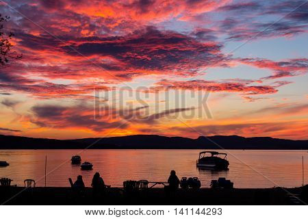 amazing sunset over lake Quebec Canada with peoples silhouette looking at it