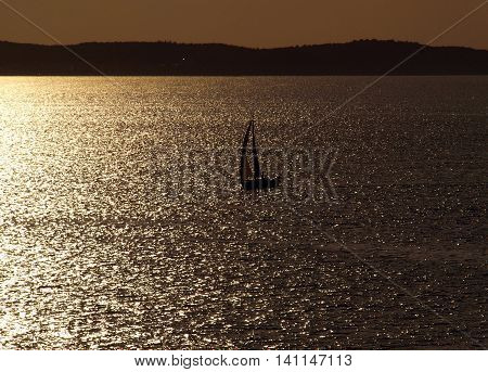 Lonely sail. Baltic Sea, Poland - August 18, 2009 Lonely sail boat in the Baltic Sea in the glow of the setting sun.
