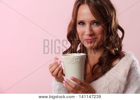 Attractive fall girl long hair holding white mug with coffee warm beverage. Woman warming herself on pink