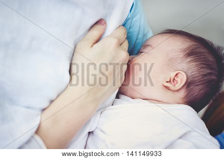 Closeup Portrait Of Mother Breastfeeding Her Newborn Baby With Breast Milk. Vintage Tone.