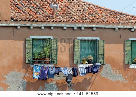 Clothes hung between windows in a house in Murano, Venice, Italy