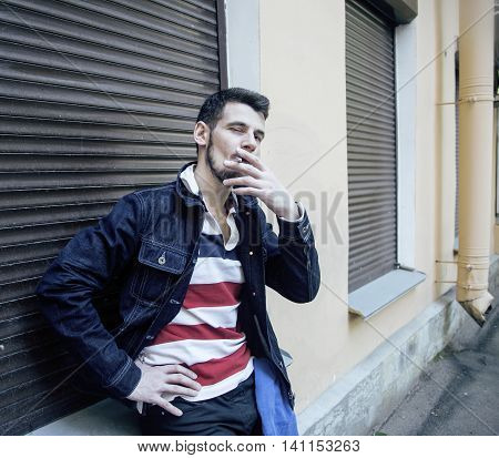 middle age man smoking cigarette on backjard, stylish tough guy, lifestyle real people concept