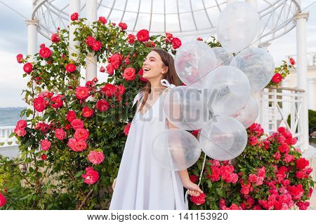 Young smiling beautiful girl with balloons outdoors over flowers background