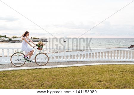 Cheerful lovely young woman riding bicycle on promenade