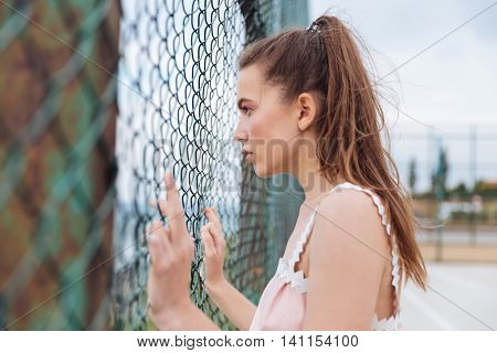 Pensive young woman standing and looking through chain link fence