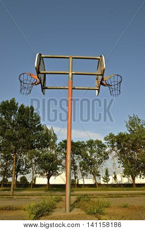 Back to back basketball standards, backboards, hoops, and chain nets in a weedy court.