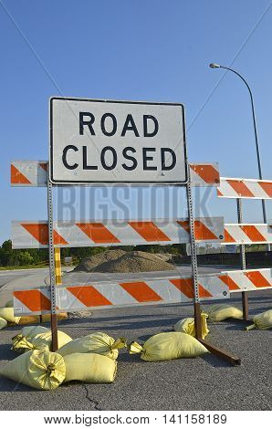 Sand bags hold sign ROAD CLOSED due to construction with sand on the pavement