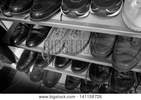 Row of Old Shoes on Shelves with Laces Black and White