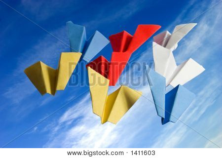 Abstract Origame Paper Planes On Cloudy Sky Background