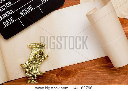 Theatrical masks and movie clapper on wooden background