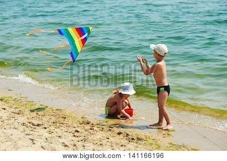 children on the beach playing with a kite