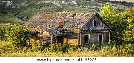 Old abandoned wooden house overgrown grass on a bright sunny summer evening closeup