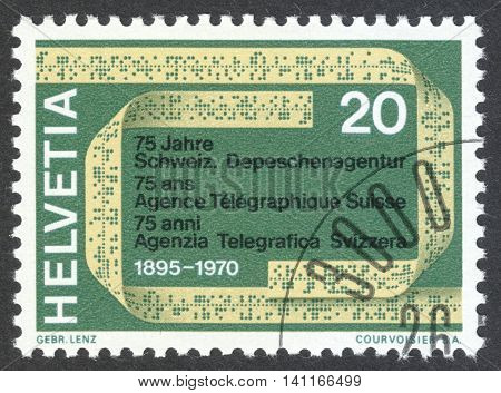 MOSCOW RUSSIA - CIRCA APRIL 2016: a post stamp printed in SWITZERLAND shows a telex tape dedicated to the 75th anniversary of the Swiss Telegraph Agency circa 1970