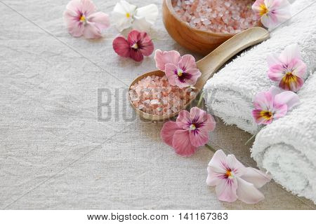 Pink sea salt and flowers Spa setting copy space background selective focus