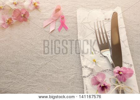 Pink ribbon day table setting with pink flowers copy space toning background