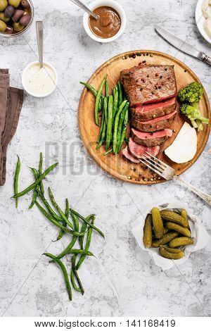 Sliced medium rare grilled steak on a wooden board on white surface with different vegetables sauces and pickles top view