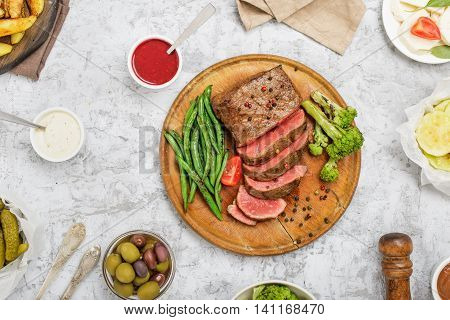Sliced medium rare grilled steak on wooden board on white surface with different vegetables sauces pickles olives and potatoes top view