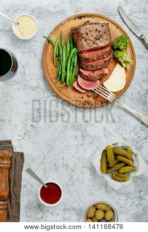 Sliced medium rare grilled steak on wooden board on white surface with different vegetables sauces olives and red wine top view place for text