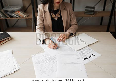 Businesswoman signing contract. Cropped image of female chief, writting on papers. Successful woman, feminist concept