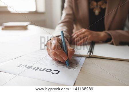 Female hand with pen completing personal information on form. Business woman signing profitable contract.