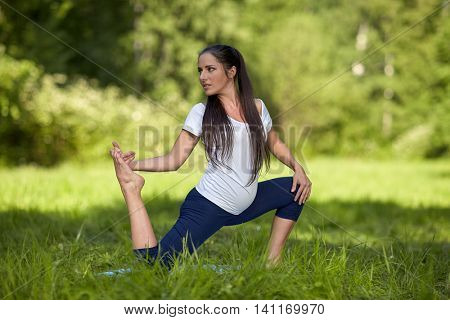 The active pregnant woman does sports exercises in a summer park. Care of health and pregnancy.