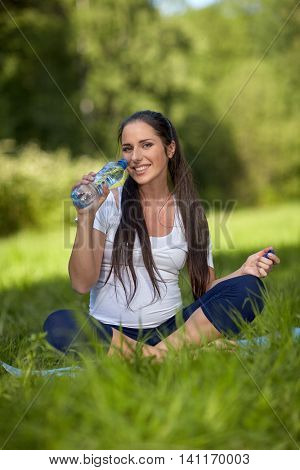 Sports pregnant woman drinks water in a summer park. Care of health and pregnancy.