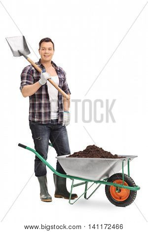 Full length portrait of a male gardener holding a shovel and posing by a wheelbarrow isolated on white background