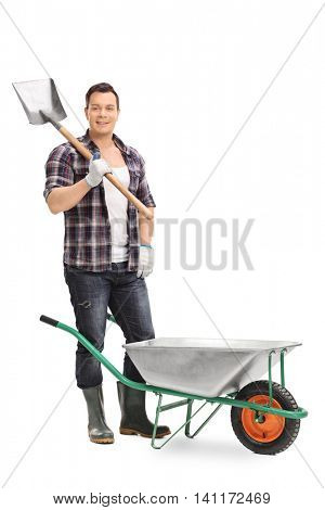 Full length portrait of a smiling gardener posing with gardening equipment isolated on white background