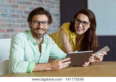 Portrait of business executive and co-worker holding digital tablet in office
