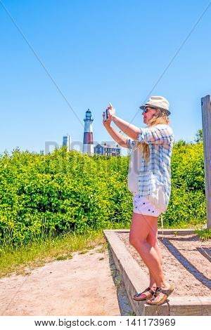 Young tourist taking photos with her cell phone at Montauk Point Lighthouse - Long Island, US