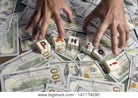 Playing cubes with a word Panic written and male hands grabbing dollars studio closeup shot
