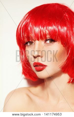 Portrait of young beautiful sexy red-haired girl with bob haircut and red lipstick