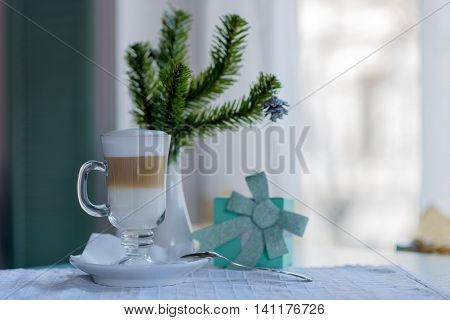 Cappucino drink in cocktail glass on winter cosy background
