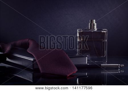 Men's fragrance on the desktop. A bottle of men's perfume on a dark background.