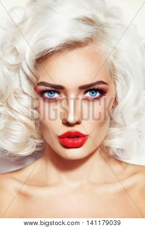 Vintage style portrait of young beautiful platinum blonde sexy woman with stylish hairdo and red lips