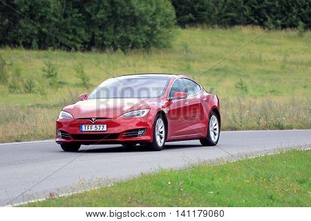 PAIMIO FINLAND - JULY 31 2016: Tesla Model S luxury sedan with the new look on rural road in South of Finland. Tesla updates also the exterior of the Model S in April 2016.