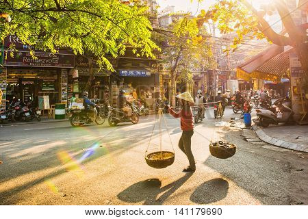 Hanoi, Vietnam - 13 January, 2015: A vendor walk into old street