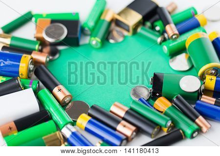 recycling, energy, power, environment and ecology concept - close up of alkaline batteries and green blank copy space
