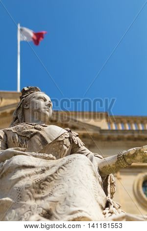 Statue of Queen Victoria Republic Square Valletta Malta Europe. With Maltese flag and the limestone National Library of Malta in background